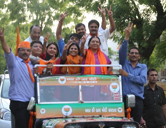 Anandiben shows the victory sign as she participates in a roadshow after the BJP win in the Lok Sabha polls