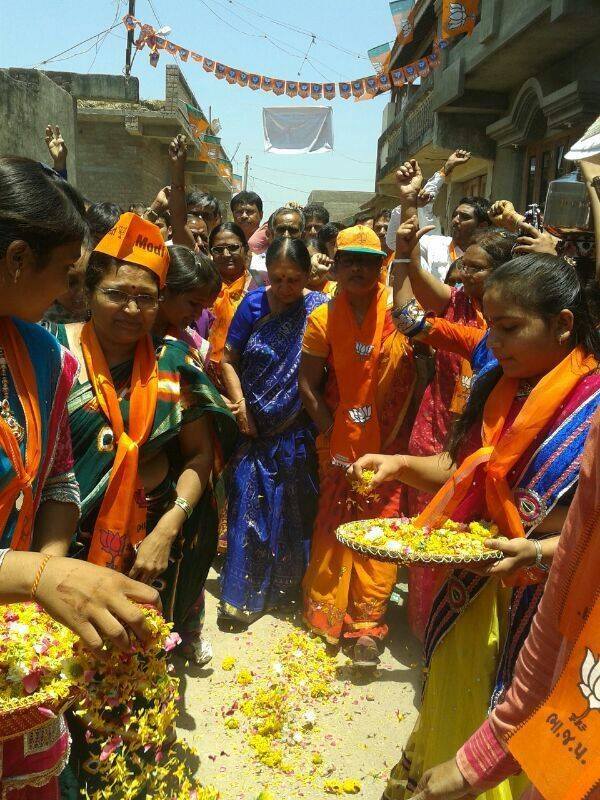 Workers of BJP's women's wing shower Anandiben with flower petals