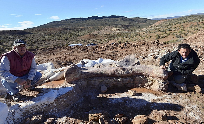 Paleontologists Jose Luis Carballido (right) and Ruben Cuneo pose next to the bones of a dinosaur at a farm in La Flecha, west of the Argentina's Patagonian city of Trelew