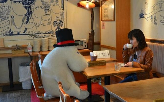 A diner sits with a stuffed toy at the Japanese cafe.