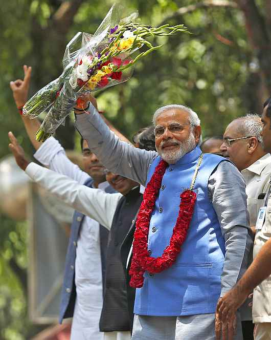 PM-designate Narendra Modi greets to supporters outside the BJP headquarters in New Delhi