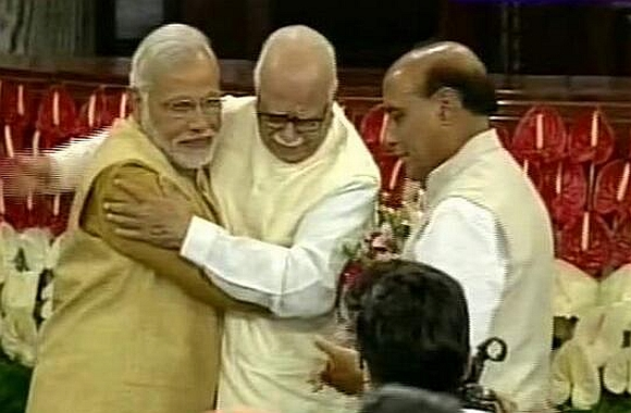 An emotional L K Advani hugs Narendra Modi in Parliament as Rajnath Singh looks on