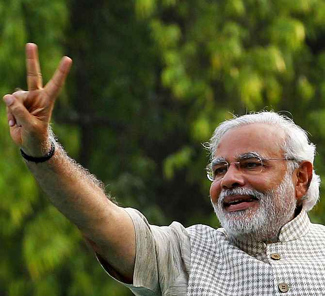 Narendra Modi waves the victory sign in Vadodara after the poll verdict was out on May 16