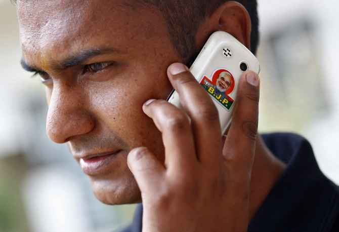 A BJP supporter speaks on his mobile phone with a picture of Narendra Modi, in New Delhi