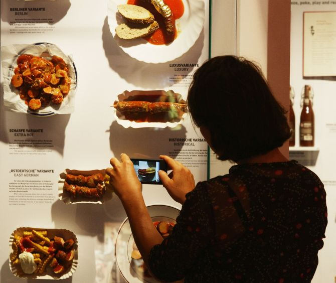 A visitor takes a snapshot of different currywurst styles at the museum.