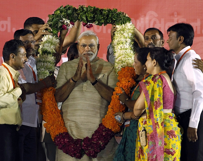PM elect Narendra Modi wears a garland presented to him by his supporters at a public meeting in Ahmedabad