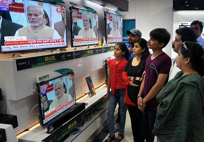 People watching swearing-in ceremony of Prime Minister Narendra Modi on TV sets at a shop