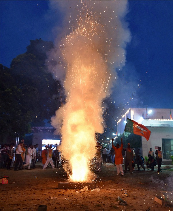 BJP workers celebrate with crackers the swearing-in of Narendra Modi as the Prime Minister at BJP head quater in New Delhi on Monday