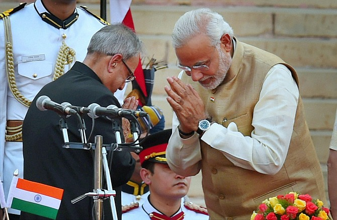 President Pranab Mukherjee greets Prime Minister Narendra Modi after administering him the oath at a ceremony at Rashtrapati Bhavan in New Delhi