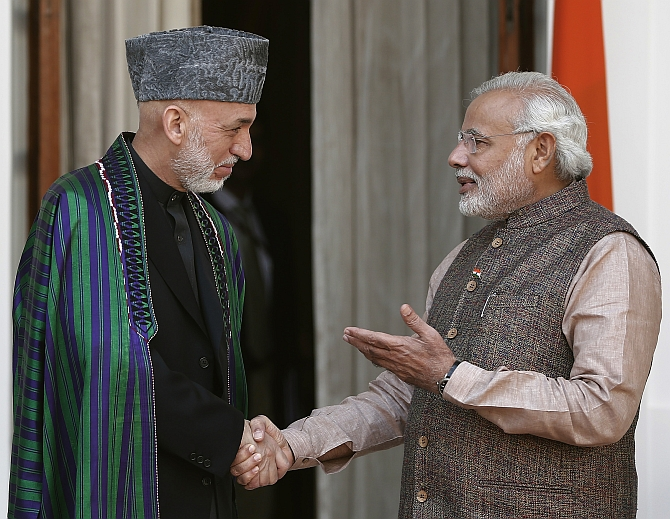 Modi shakes hands with Afghanistan's President Hamid Karzai before start of their meeting in New Delhi