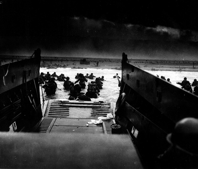 Landing on the coast of France under heavy Nazi machine gun fire are these American soldiers, shown just as they left the ramp of a Coast Guard landing boat