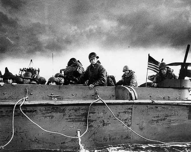 Troops and crewmen aboard a Coast Guard manned LCVP as it approaches a Normandy beach
