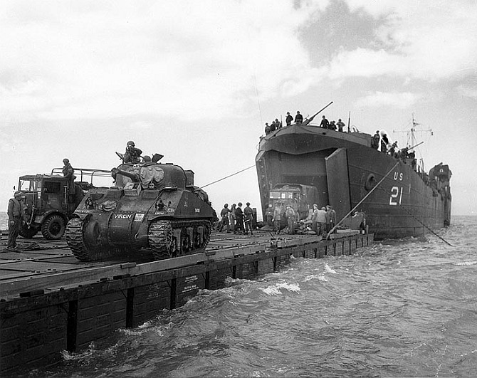 Coast Guard manned USS LST-21 unloads British Army tanks and trucks onto a 'Rhino' barge