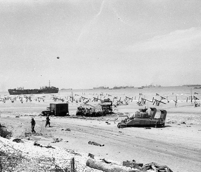 Scene on 'Omaha' beach on the afternoon of 'D-Day', June 6, 1944, showing casualties on the beach, a bogged-down 'Sherman' tank, several wrecked trucks and German anti-landing obstructions