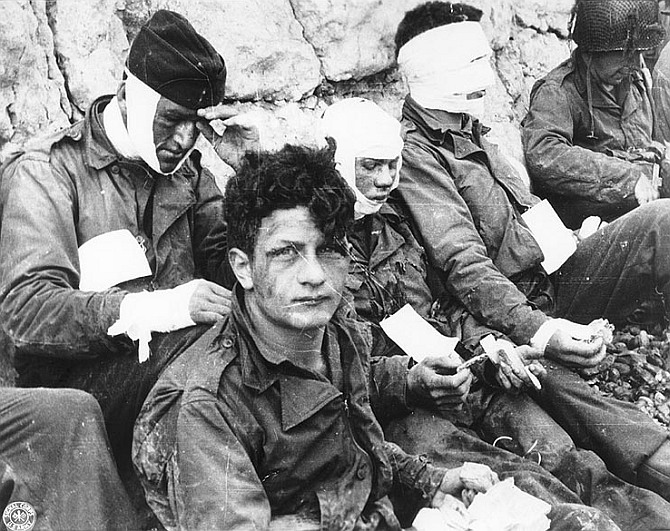 Wounded men of the 3rd Battalion, 16th Infantry Regiment, 1st Infantry Division, receive cigarettes and food after they had stormed 'Omaha' beach
