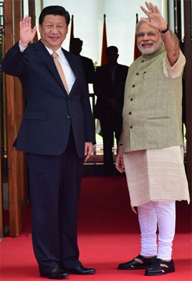 Chinese President Xi Jinping and Modi waves to the crowds during the former's visit to India earlier this year.