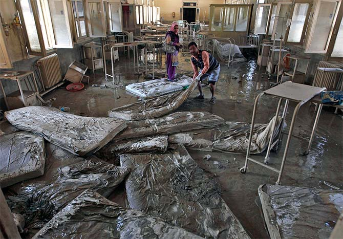 Muddied mattresses being removed from a hospital in Srinagar.
