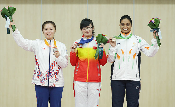 Gold Medalist Mengyuan Zhang of China (centre), Silver Medalist Jung Jee-Hae of South Korea (left), and Bronze Medalist Shweta Chaudhry of India (right) celebrate on the podium after winning their medals in the 10m Air Pistol Women's event