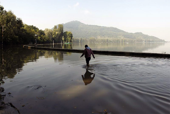 A man wades in flood waters near Dal Lake