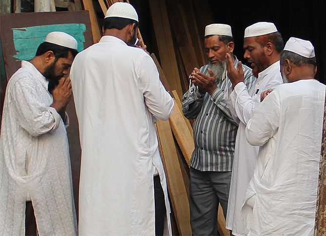 A group of Muslims in Hashimpura offer prayers. In the centre is Mohammed Naeem, one of the survivors from the 1987 massacre. Photograph: Uttam Ghosh/Rediff.com