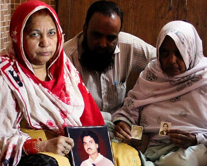 Zulfikar Nasir gives moral support to Shamim Bano, left, who is holding a photograph of her only brother, who was shot by the PAC. Zarina, right, who never speaks, with photographs of her husband and son. Both were killed in 1987. Photograph: Uttam Ghosh/Rediff.com