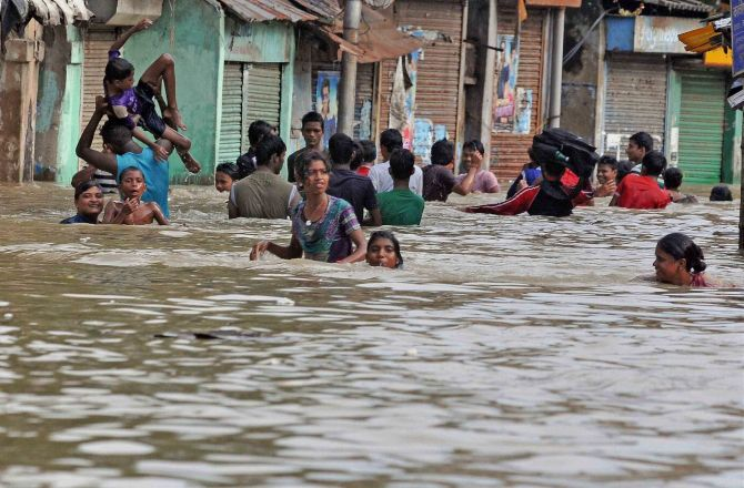 Locals wade through a waterlogged road in Kalighat, Kolkata