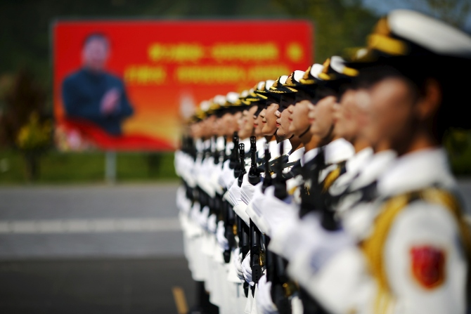 A billboard with Chinese President Xi Jinping behind People's Liberation Army soldiers in Beijing. Photograph: Damir Sagolj/Reuters