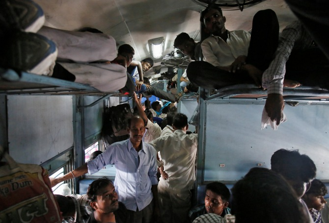 Passengers sit inside a crowded stationary train at a railway station in New Delhi.