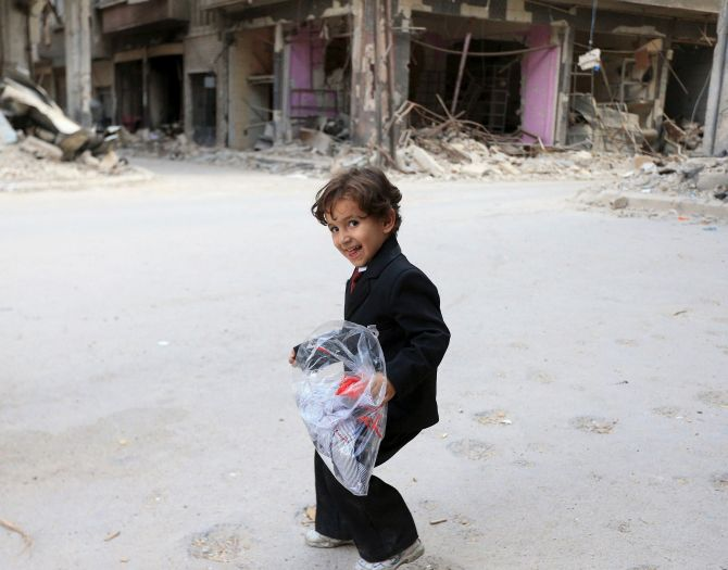 A boy carries a bag of new clothes in Jobar, a suburb of Damascus, Syria. Photograph: Bassam Khabieh/Reuters