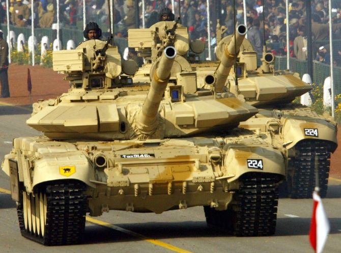Indian soldiers sit atop T-90 tanks.