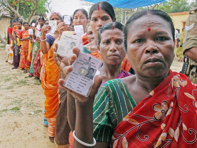 Women show their voter cards at a polling booth during the assembly election at Bandhlodanga in Birbhum, Bengal. Photograph: PTI