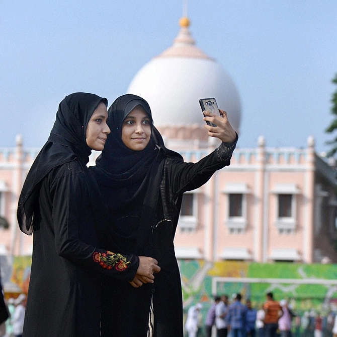 Muslim women click a selfie at the Taj