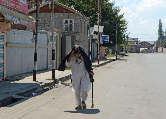 An elderly man walks on a deserted street in Srinagar. Photograph: Umar Ganie