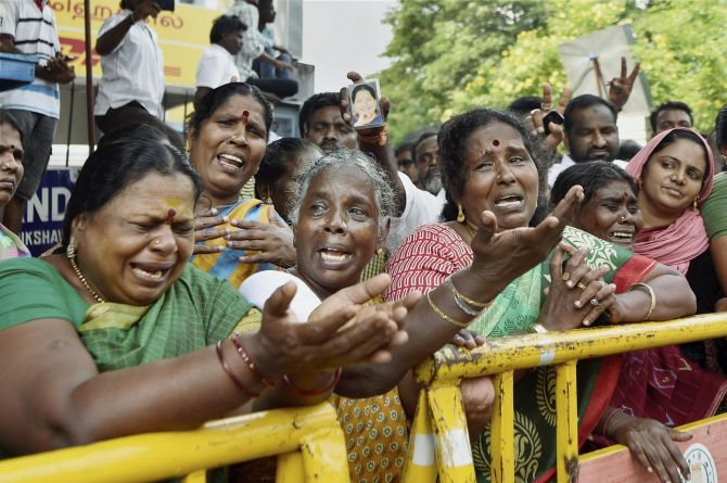 Supporters of Tamil Nadu Chief Minister Jayalalithaa cry in front of Apollo hospital in Chennai