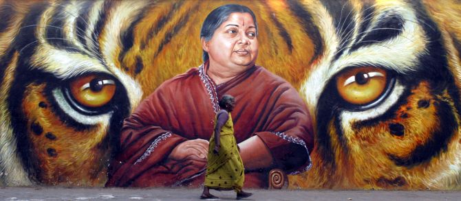 A woman walks past a Jayalalithaa poster