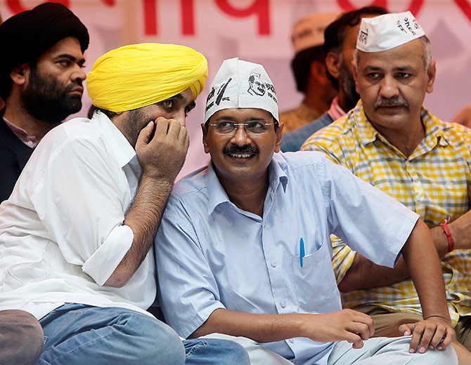 Delhi's chief minister and Aam Aadmi Party (AAP) chief Arvind Kejriwal listens to his party leader and MP Bhagwant Mann during a rally in 2014