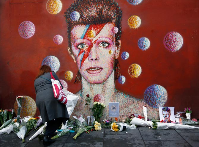 A woman leaves a bouquet at a mural of David Bowie in Brixton, south London, January 11, 2016. Photograph: Stefan Wermuth/Reuters
