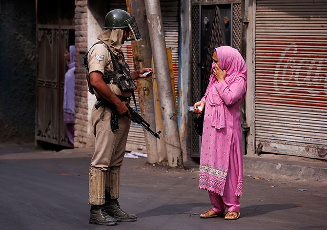 A woman shows her identity proof to a soldier in Kashmir