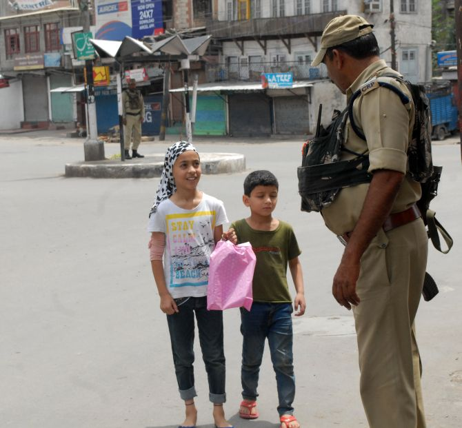 Security personnel question children on a deserted street in Srinagar. Photograph: Umar Ganie