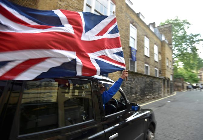 A taxi driver holds a Union flag in London