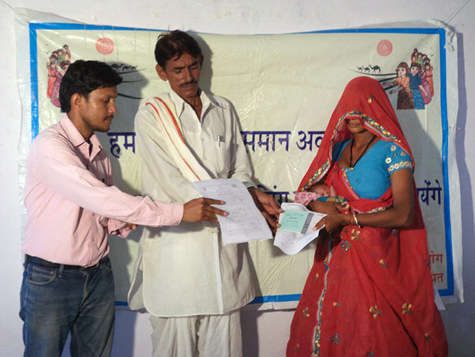 A bank account passbook, in the name of the girl child, and the birth certificate is handed over to the mother in Dausa, Rajasthan.