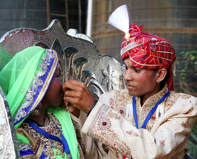 A groom helps his bride fix her nose ring.