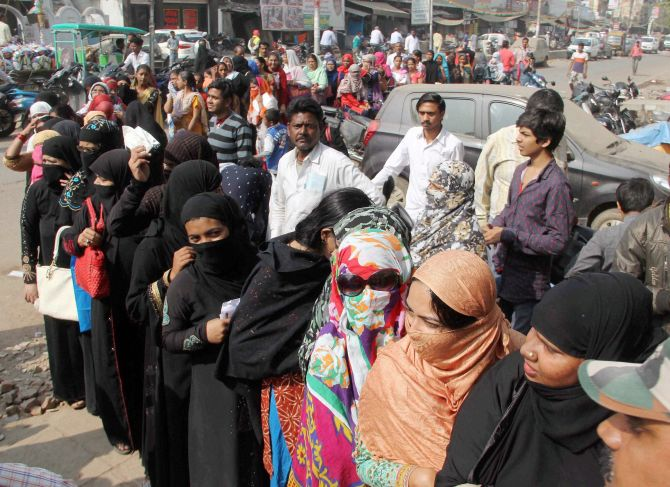 Women queue-up outside a bank to exchange their old notes