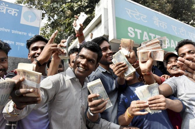 PATNA: People show money withdrawn from an ATM. Photograph: PTI Photo