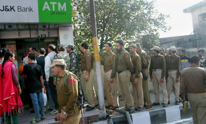 JAMMU: Jammu & Kashmir police personnel stand with other people in a queue outside an ATM. Photograph: PTI Photo