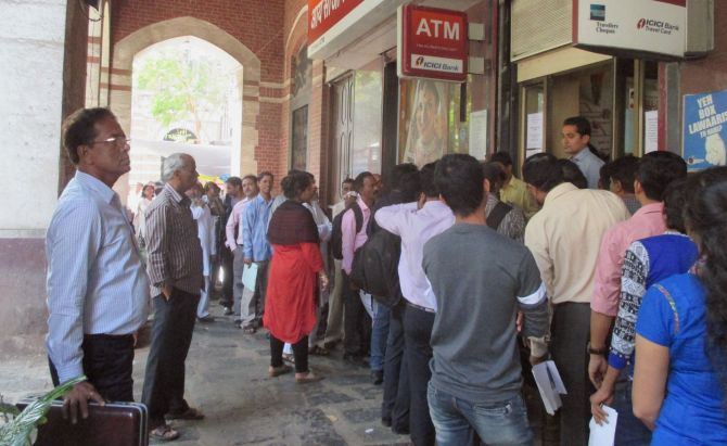 People queue up for money outside a bank in Mumbai