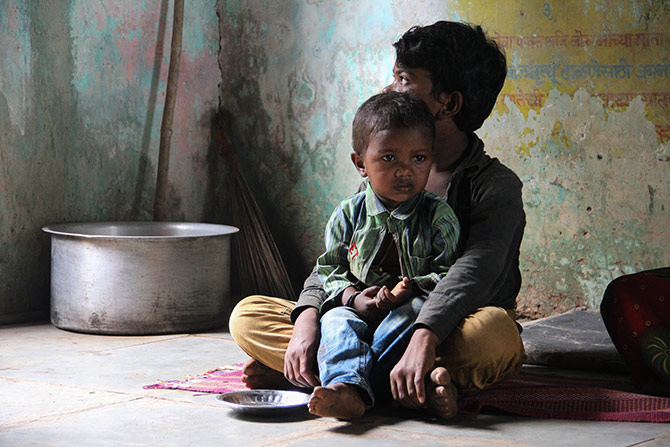 A pensive child awaits the afternoon meal. Till then he decides to sit quietly on his brother's lap.