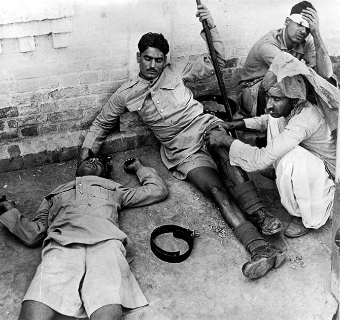 Three wounded Indian policemen receiving treatment following the riots in Lahore.