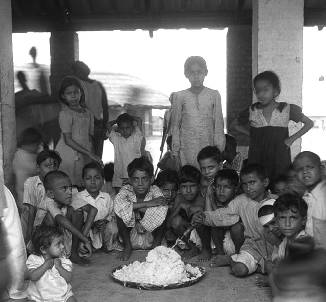 At the Kingsway refugee camp, children help themselves to the rice provided for their meal.