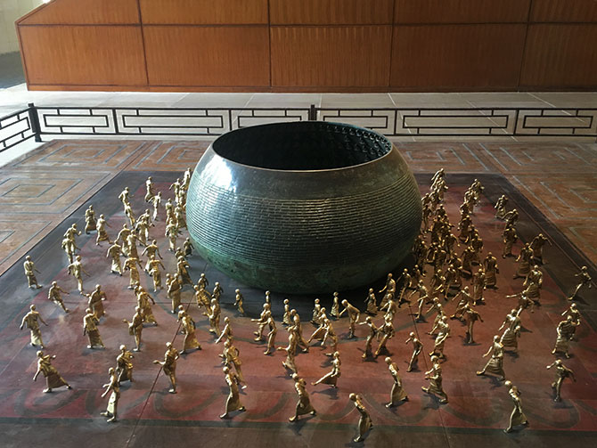 Installation depicting Buddha's begging bowl surrounded by monks
